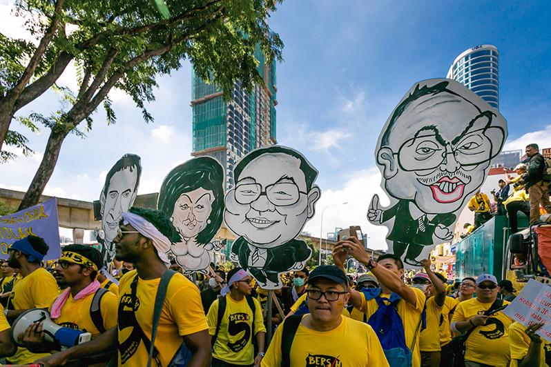 Protesters hold placards with caracature depicting Najib Razak, Rosmah Mansur, Jho Low.